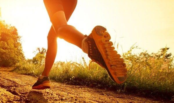 Blog de la imagen de las piernas de la dama y los pies como ella corre en un camino con el sol naciente